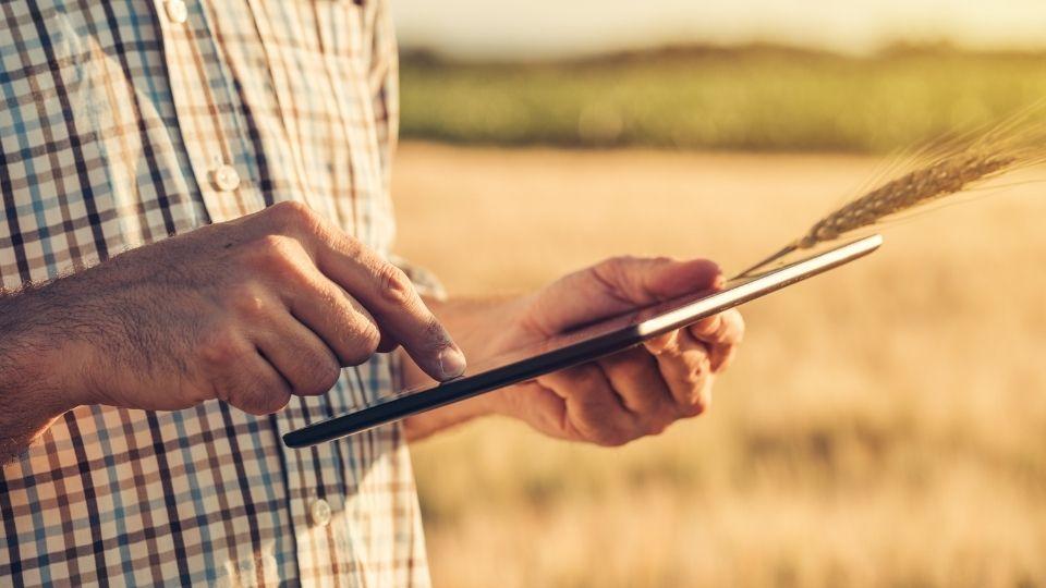 Homem no meio do campo com um tablet em mãos